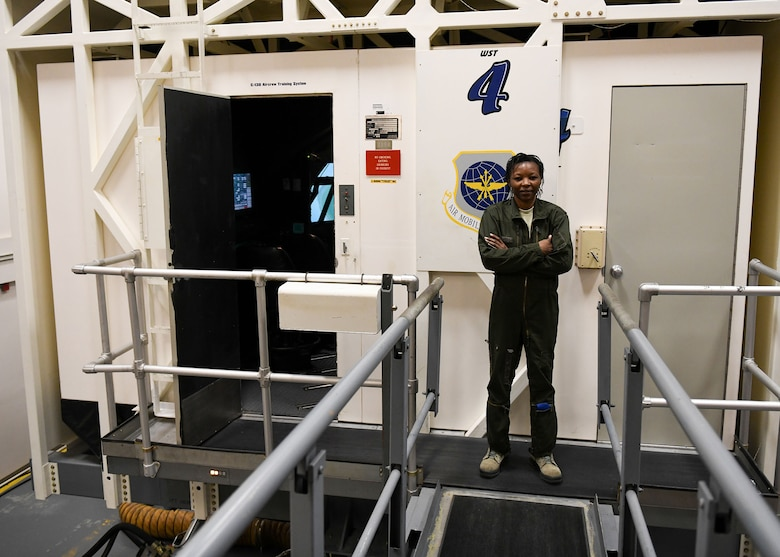 A woman stands in front of a C-130 simulator.
