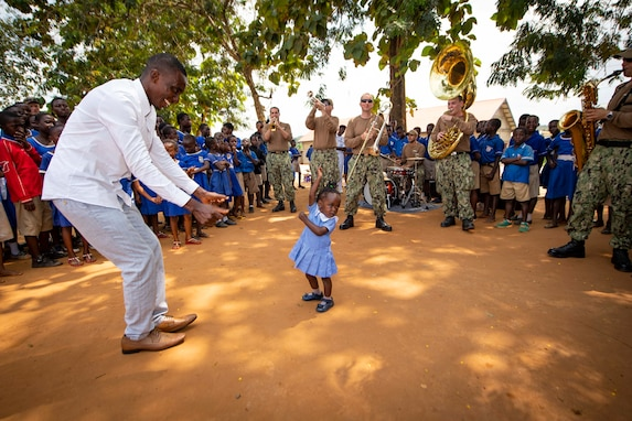 "Students at St. John's Anglican Primary School dance as the U.S. Naval Forces Europe Band ""Topside,"" embarked aboard the Spearhead-class expeditionary fast transport ship USNS Carson City (T-EPF 7), performs during a community relations project in Takoradi, Ghana, July 23, 2019."