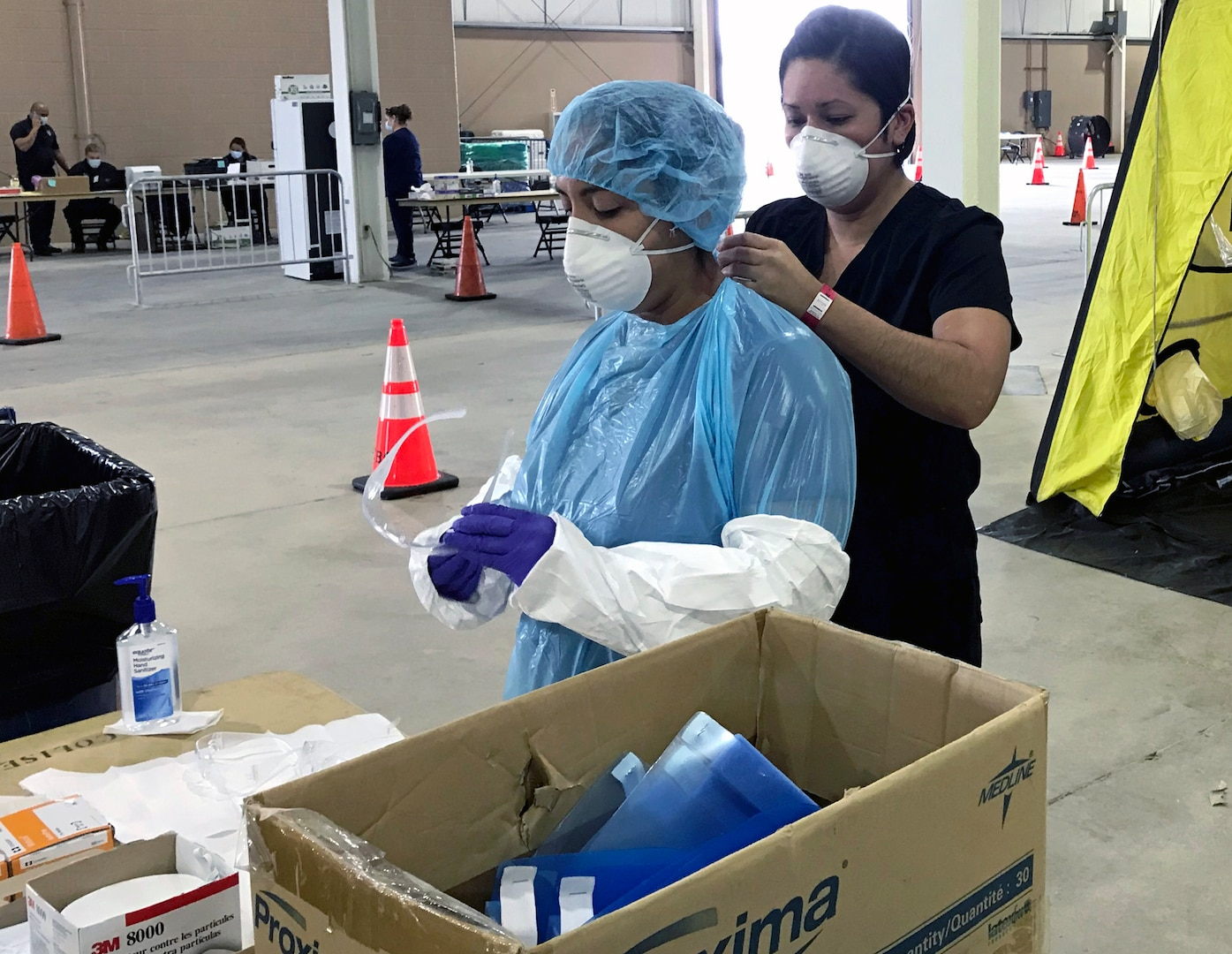 Capt. Gabriella Torres assists Capt. Denise Rodriguez with securing her personal protective equipment.