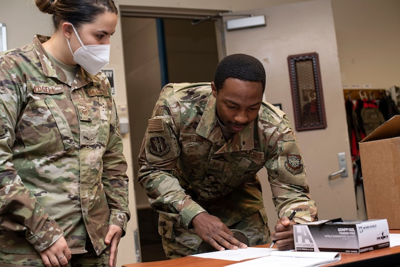 A female Airmen with a white face mask on supervises a male Airmen signing a document in front of a box full of black face masks