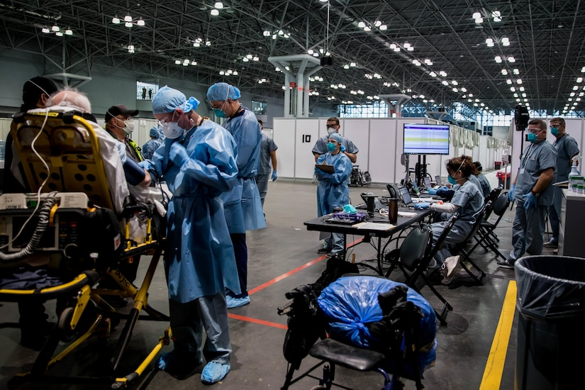 Army Spc. Daniel Fields, assigned to the 9th Hospital Center, takes a patient's blood pressure reading in the Javits New York Medical Station (JNYMS).