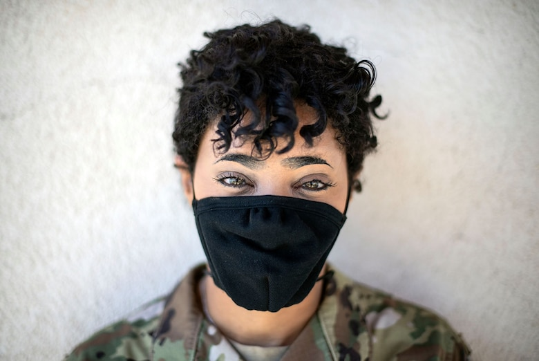 A female Airman in uniform looks directly at the camera with a black face mask on. It's sunny.