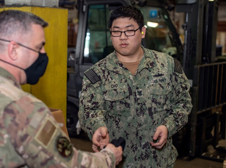 A male Airman with a black face mask on hands off another black face mask to a male Sailor in a warehouse-type environment