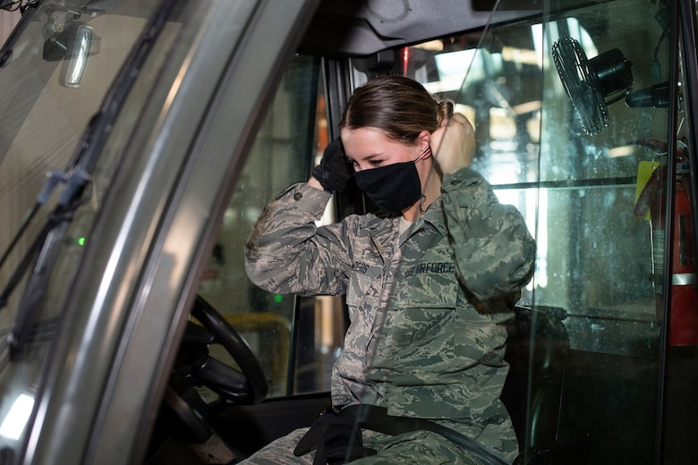 A female Airman in a forklift dons a black face mask inside of a warehouse