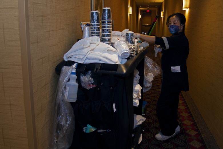 Ma Luisa Jones, Presidential Inn Housekeeping supervisor, uses supplies from her cart to clean and disinfect the rooms at the Temporary Lodging Facility on Joint Base Andrews, Md., April 13, 2020. The rooms and common areas are sanitized multiple times a day in efforts to keep the staff and guests safe from the coronavirus disease.