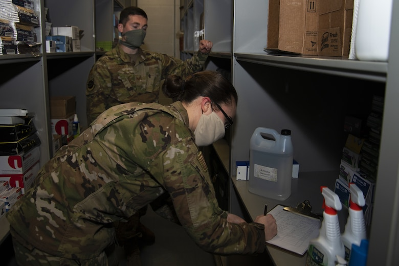 Staff Sgt. Joshua Grudznske, 11th Security Support Squadron supply NCO in-charge, and Senior Airman Caitlyn Truax, 11th SSPTS supply technician, verifies information on the sign out log for the hand sanitizer on Joint Base Andrews, Md., April 20, 2020. A sign out log is kept to track and ensure that units are able to get the supplies needed.