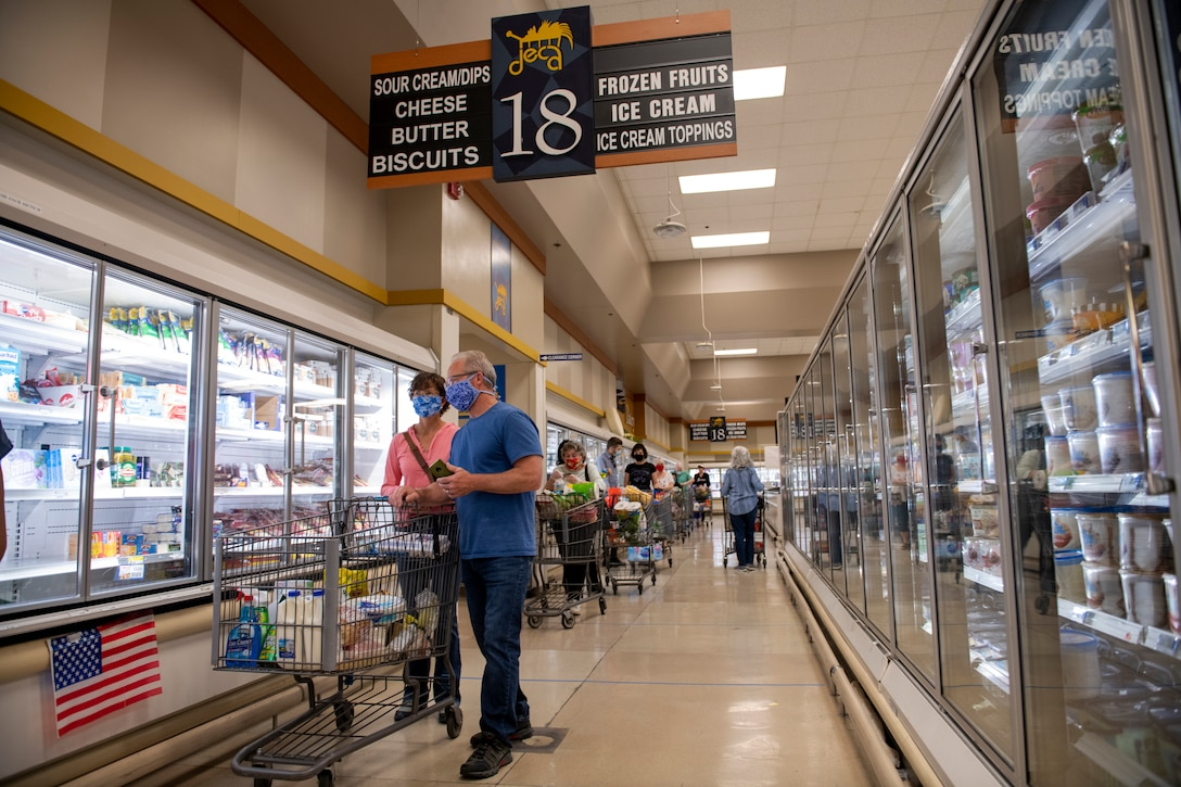 Shoppers wear masks as they wait to pay for their groceries April 16, 2020, inside the commissary at Travis Air Force Base, California. Commissary patrons must wear masks while shopping to prevent the spread of the new coronavirus. (U.S. Air Force photo by Tech. Sgt. James Hodgman)