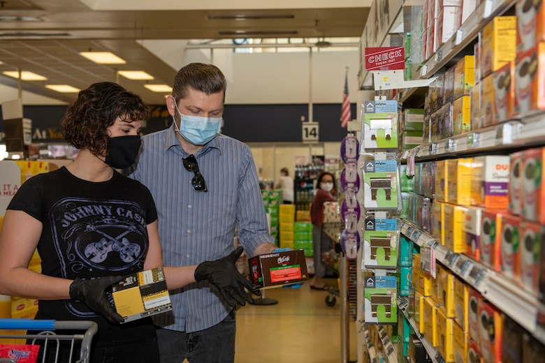 U.S. Air Force Senior Airman Nichole Krinberg, left, 60th Aerial Port Squadron air transportation journeyman, shops for coffee April 16, 2020, with her husband, John Christ, right, inside the commissary at Travis Air Force Base, California. Since the coronavirus pandemic, some food and household goods such as toilet paper and paper towels have become increasingly scarce. (U.S. Air Force photo by Tech. Sgt. James Hodgman)