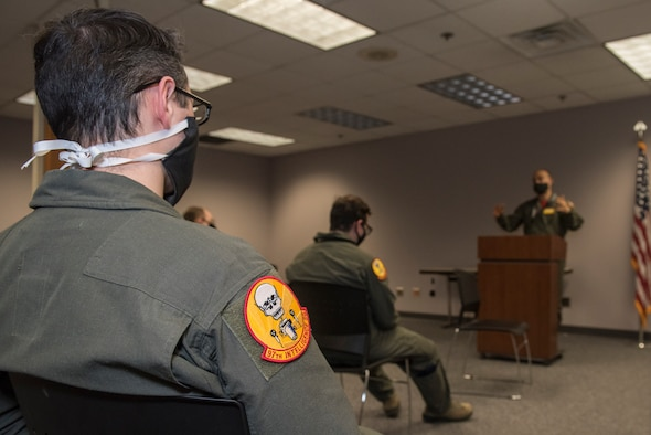 service members listen to a briefing wearing cloth masks and social distancing.