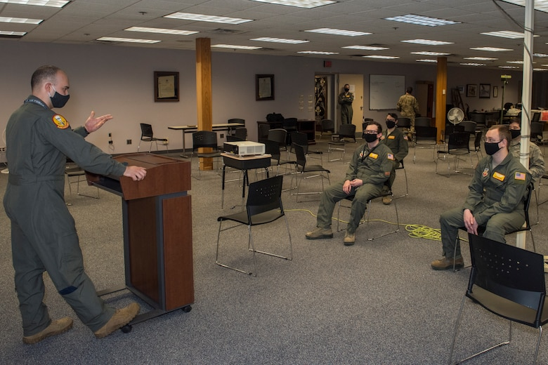 A service member briefs four service members while the group practices social distancing and wears cloth masks