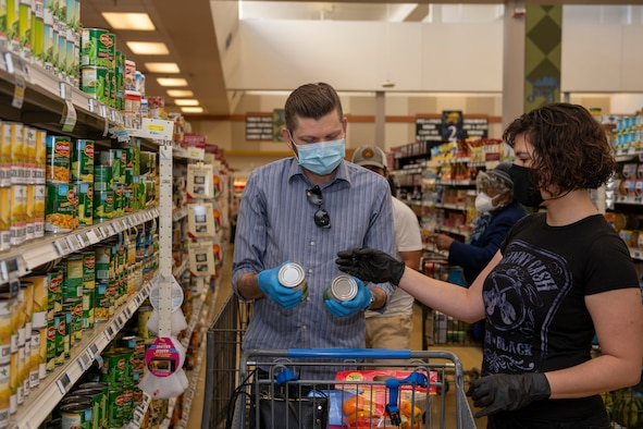 John Christ, left, husband of U.S. Air Force Senior Airman Nichole Krinberg, right, 60th Aerial Port Squadron air transportation journeyman, shops for vegetables April 16, 2020, with Krinberg, inside the commissary at Travis Air Force Base, California. Since the coronavirus pandemic, some food and household goods such as toilet paper and paper towels have become increasingly scarce. (U.S. Air Force photo by Tech. Sgt. James Hodgman)