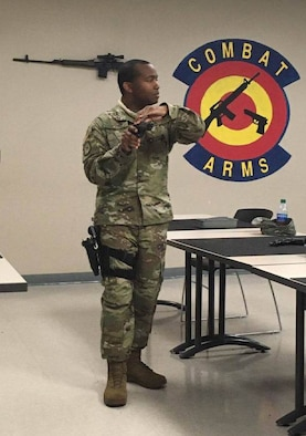 Tech. Sgt. Derrick Tolbert, 403rd Security Forces Squadron combat arms noncommissioned officer in charge, shows the proper procedures for handling a M9 firearm during a class April 9, 2020. The students were then taken to the indoor firing range to do the weapon qualification course at Keesler Air Force Base, Miss. (U.S. Air Force courtesy photo)
