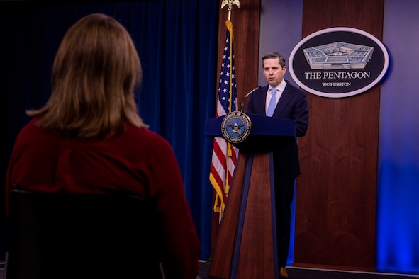 A man stands at a podium and talks to people who are practicing social distancing.