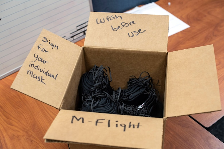 """A cardboard box with the phrases """"wash before use,"""" """"Sign for your individual mask,"""" and """"M-Flight"""" written on it sits on a wooden table with black face masks in it"""