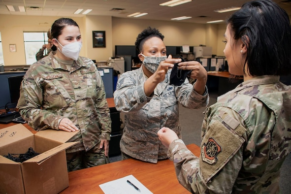 Two female Airmen, one with a white face mask and one with a camo face mask on, instructs a third face mask-less Airmen on how to don one.