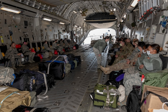 U.S. Air Force personnel from the 349th Medical Group prepare for takeoff inside a U.S. Air Force C-17 Globemaster III from March Air Reserve Base, California, April 22, 2020, at Travis Air Force Base, California. The aircraft provided deployment airlift for 349th MDG personnel from Travis AFB to New York in support of a short-notice COVID-19 mission. (U.S. Air Force photo by Heide Couch)