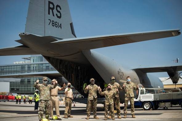 Airmen and Sailors stand by C-130 with COVID-19 medical supplies.