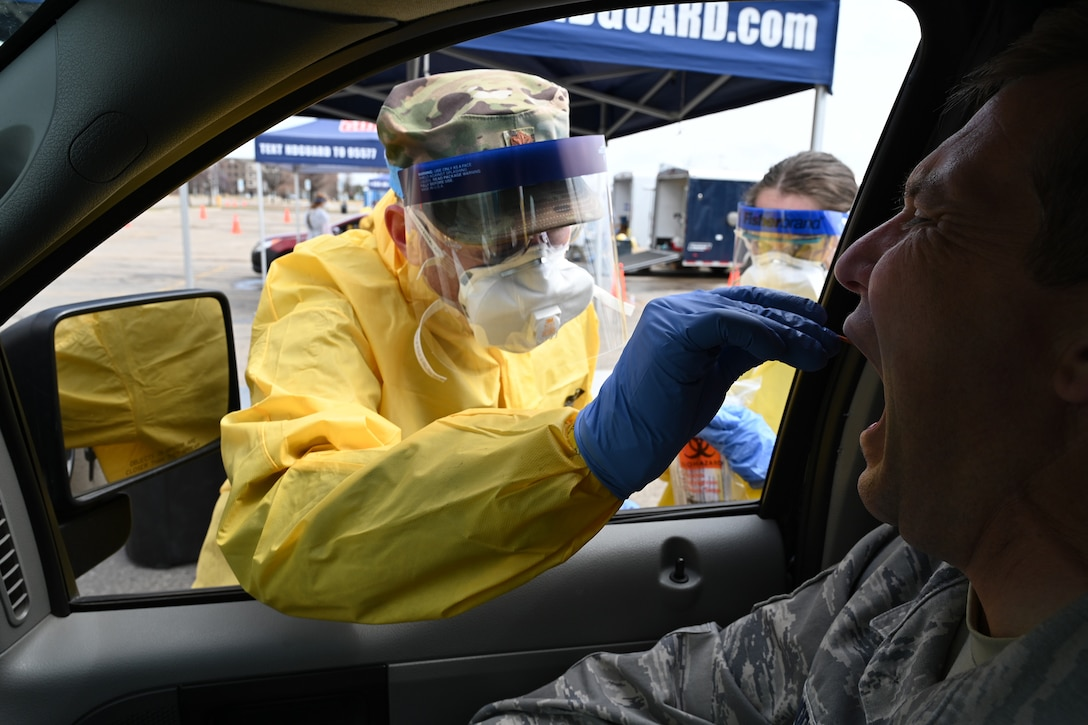 U.S. Air Force Maj. Chad Brooks, of the 119th Medical Group, takes a sample swab from an asymptomatic volunteer who is taking a COVID-19 test in the parking lot of the Alerus Center, Grand Forks, North Dakota, April 23, 2020. He's wearing personal protective equipment to stay safe while he works, and to help prevent the spread of COVID-19 while testing people as they drive through in their vehicles. He is just one of the many North Dakota National Guard members partnering with the North Dakota  Department of Health and other civilian agencies in support of the community response to the COVID-19 pandemic. (U.S. Air National Guard photo by David H. Lipp)