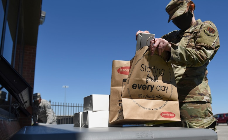 A U.S. Air Force Airman assigned to the 1st Fighter Wing picks up food for coworkers during a 1st Fighter Friday lunch at Joint Base Langley-Eustis, Virginia, April 22, 2020.
