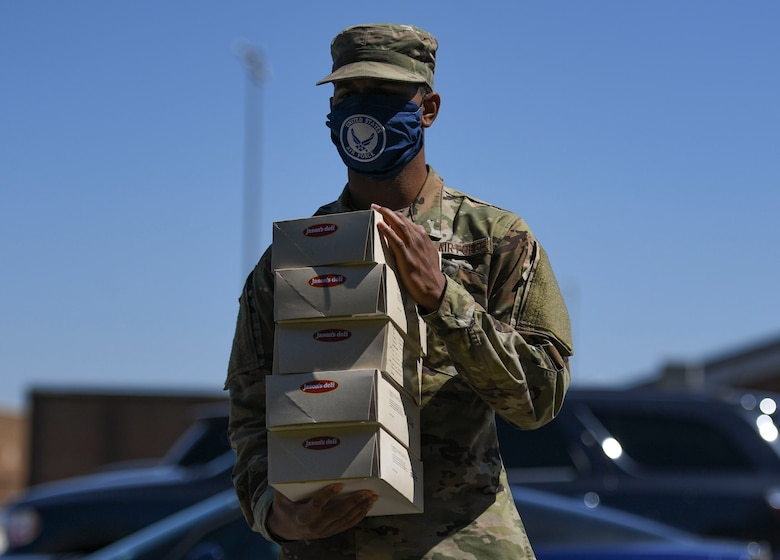 A U.S. Air Force Airman assigned to the 1st Fighter Wing carries boxed lunches back to his work area during a 1st Fighter Friday lunch at Joint Base Langley-Eustis, Virginia, April 22, 2020.