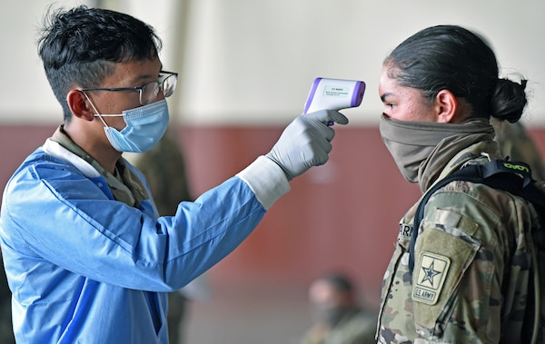 A Soldier has her temperature checked