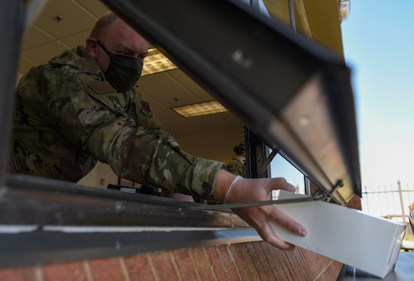 U.S. Air Force Capt. Ryan Ayers, 633rd Air Base Wing chaplain, passes a boxed lunch through a window during a 1st Fighter Friday lunch at Joint Base Langley-Eustis, Virginia, April 22, 2020.