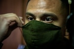 A Marine puts on a green cloth face mask to protect against the coronovirus