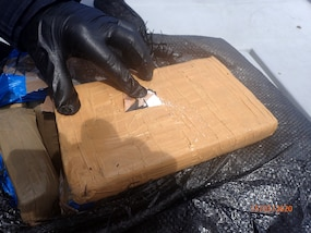 Bale of cocaine being opened.
