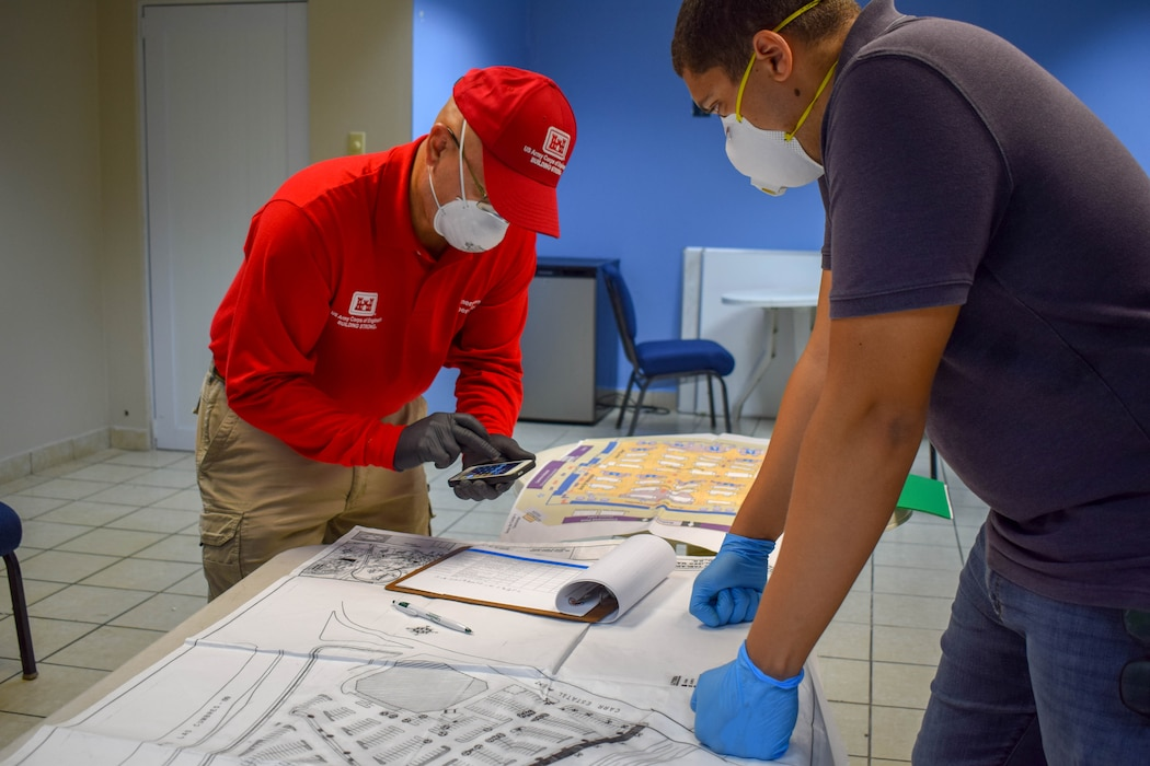 Ramon Collazos wearing a red USACE shirt imputing numbers on a calculator while looking at map layout on the table as Alejandro Feliz  observes.