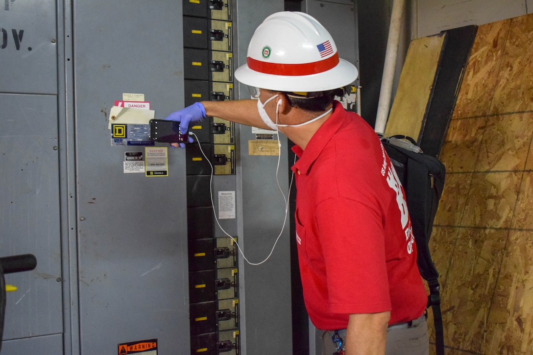 Hector Ortiz wearing a red USACE shirt and white hardhat holding a cell phone to an electrical panel.