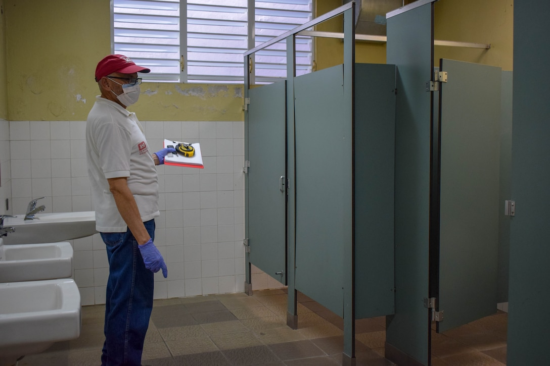 Marcial Garay is holding a clipboard as he stands in front of the bathroom stalls.
