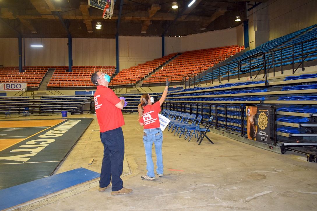 USACE employees pointing at the ceiling while standing at the floor of the coliseum