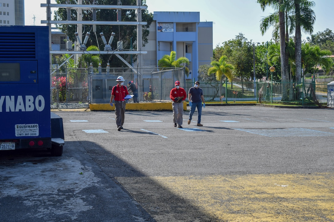 Three male USACE employees walking on the parking lot while conducting an assessment.
