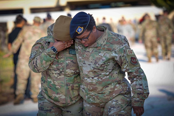Photo of two Airmen consoling each other