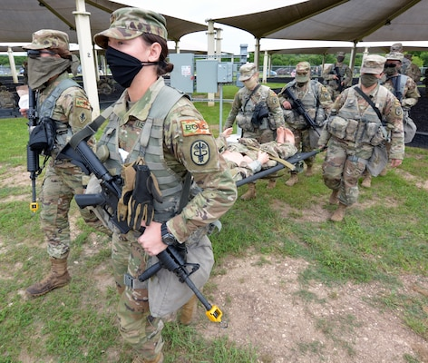 Basic Officer Leadership Course students move a simulated causality while adhering to tactical dispersion during the COVID-19 response at a field training exercise held at Joint Base San Antonio-Camp Bullis April 14.