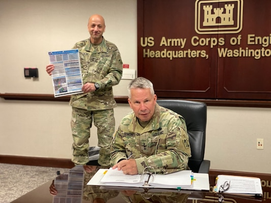 Lt. Gen. Todd Semonite, chief of engineers and U.S. Army Corps of Engineers commanding general, signs a Chief's Report for the New York and New Jersey Harbor Anchorages Study at headquarters in Washington, April 23, 2020. Holding up the study's placemat is Maj. Gen. Scott Spellmon (background), USACE deputy commanding general for civil and emergency operations.