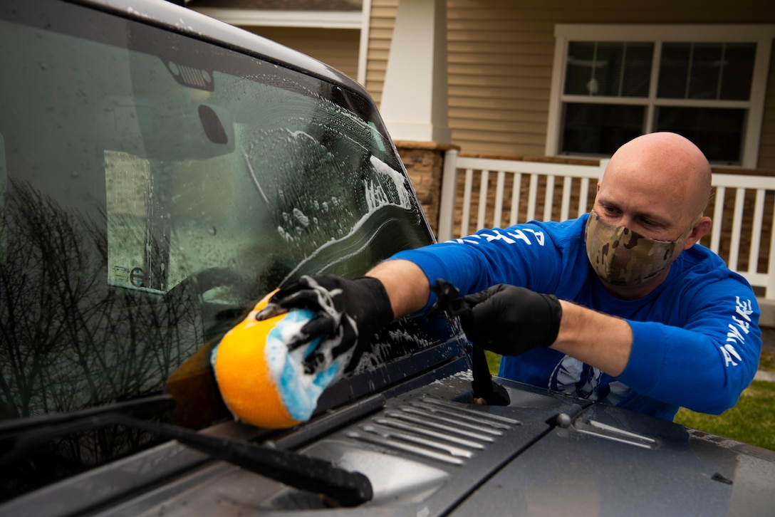 U.S. Air Force Tech. Sgt. Joshua Armstrong, 366th Operation Support Squadron radar approach control supervisor, cleans a car, April 22, 2020, at Mountain Home Air Force Base, Idaho. Airmen from the 366th OSS have been giving back to the community by helping do day-to-day tasks for families during the COVID-19 pandemic. (U.S. Air Force photo by Airman 1st Class Andrew Kobialka)