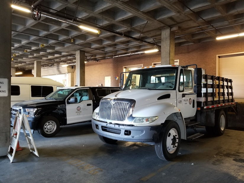 White flatbed truck with brown stakes parked in a parking structure next to a pickup and an a frame sign