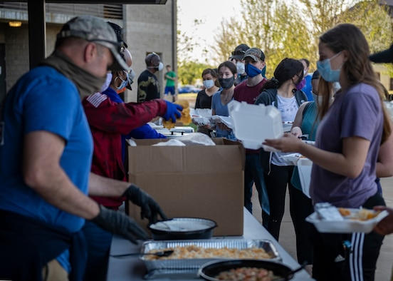 Airmen receive food from members of the Chaplain Corps and dorm leadership.