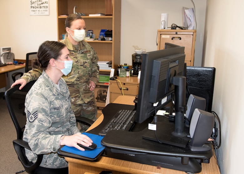 Two Airmen from Public Health stand in front a computer wearing face masks