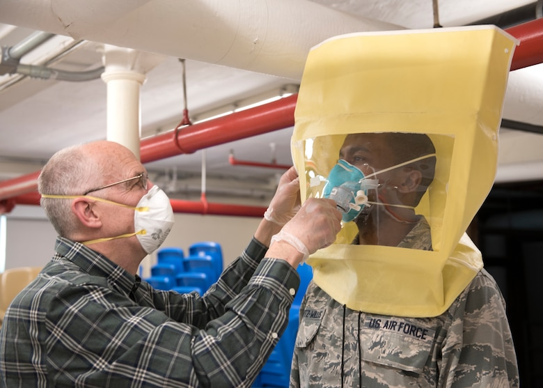 An Airman conducts a mask fitting test with a force health protection officer