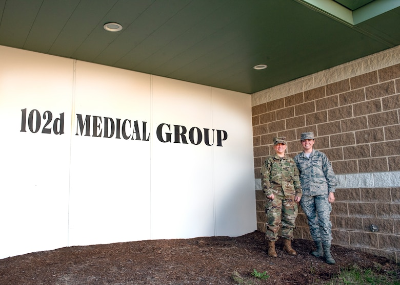 Two Airmen from Public Health stand in front of the 102nd Medical Group building at Otis Air National Guard Base, Mass.