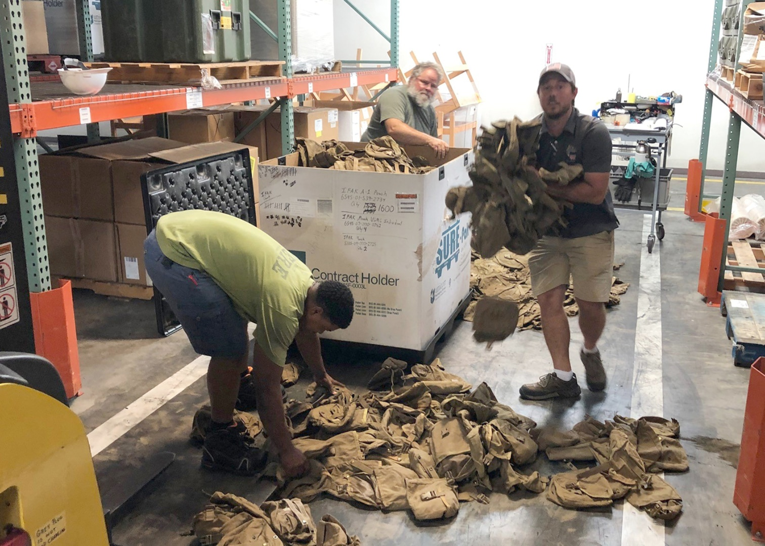 Colin Light (rear), Brian Licht (center) and Paul Turner (front), count pouches for carrying first aid supplies turned in at Camp Lejeune, North Carolina, during the first wall-to-wall inventory of all DLA Disposition Services sites.