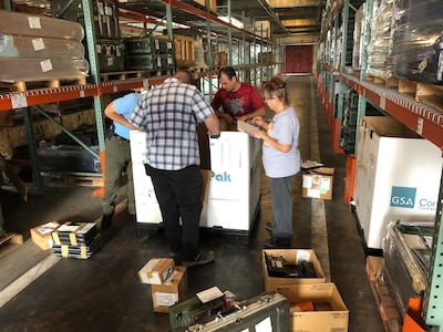 """Tommy Martorana (left), Lucas Grant (left center) and Robert Repasi (right center) check through items in a container at Camp Lejeune, North Carolina, as Sharon """"Cher"""" Burke (right) tracks the information during the first wall-to-wall inventory of all DLA Disposition Services sites."""