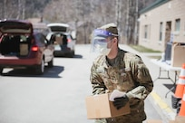 Sgt. Zachary Paquin, a fire directions specialist with the New Hampshire Army National Guard, distributes food at a mobile food drive at in Colebrook, N.H.