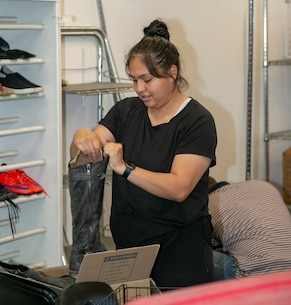Cpl Ana Santiago, inspector clerk with the Command Inspector General's Office, prepares a boot for display during the NMCRS Thrift Store move in April 18. Santiago was one of about 20 Marines and civilians who volunteered their time to assist with the relocation.