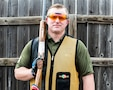 white male in green shirt and yellow and black vest wearing orange lens glasses, shooting gloves and hearing protection holds a rifle.