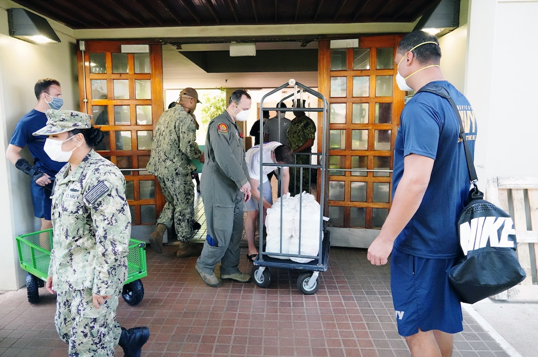 U.S. Navy Sailors and U.S. Air Force Airmen deliver meals from the Hale Aina Dining Facility to newly arrived personnel placed on restriction of movement on Joint Base Pearl Harbor-Hickam, Hawaii, April 16, 2020. Volunteers with the COVID-19 Support Team distributed meals and essentials to ROM military personnel in the midst of the COVID-19 pandemic. (U.S. Air Force photos by Airman 1st Class Erin Baxter)