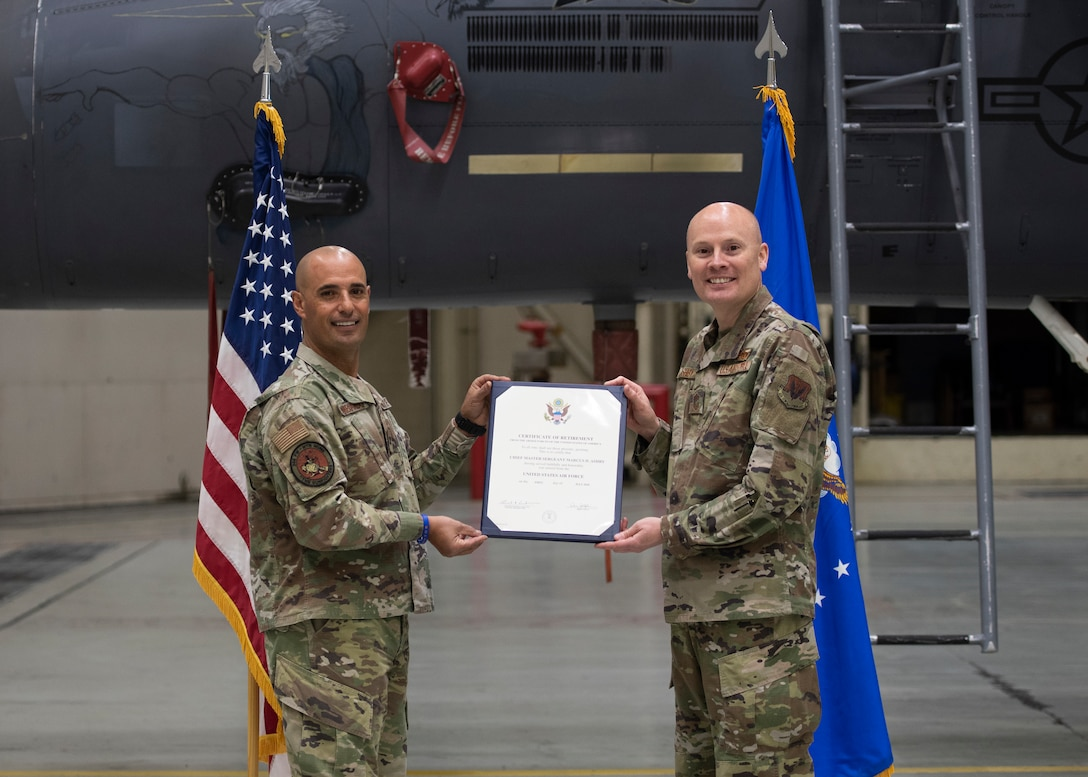 U.S. Air Force Col. Tony Lombardo, 366th Fighter Wing Chief of Staff, presents Chief Master Sgt. Marcus Ashby, 366th Fighter Wing A4 superintendent, the certificate of retirement April 16, 2020, on Mountain Home Air Force Base, Idaho. Due to the COVID-19 pandemic, Ashby came up with the idea of conducting a virtual retirement ceremony through video clips, providing a unique ceremony that not only acknowledges his career but also adapts to the changes of MHAFB. (U.S. Air Force photo by Airman 1st Class Akeem K. Campbell)