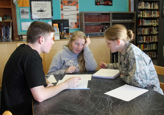 Image of three people at a table studying